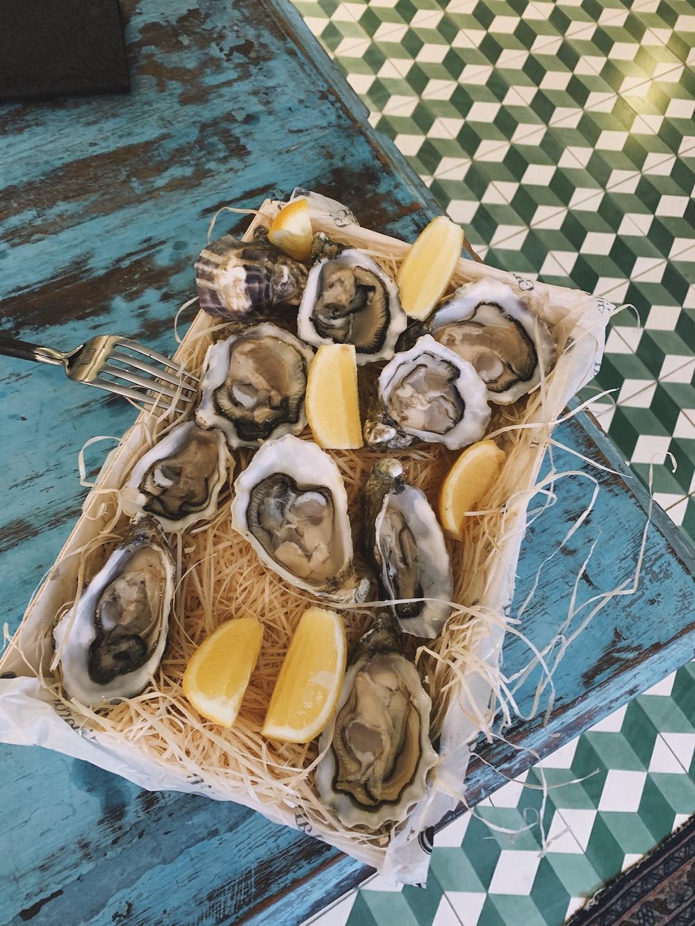 Heerlijke oesters slurpen doe je bij Bar Pêche. Maar wat nou als we je vertellen dat ze de oesters ook bij je thuis bezorgen? De seafoodbar in de Foodhallen leveren de oesters uiteraard geopend, mét citroen en vinaigrette. Ook lekker: bestel er wat zuurdesembrood bij!